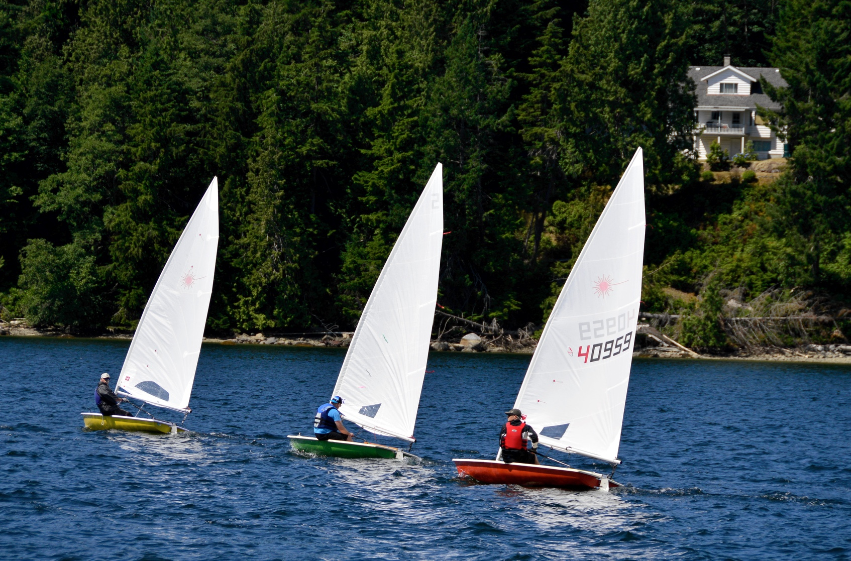 Kevin Mcevoy, left, Ken Olson, center, Brian Fournier, right, racing in the 6th Annual Poise Cove Regatta July 16th, 2017