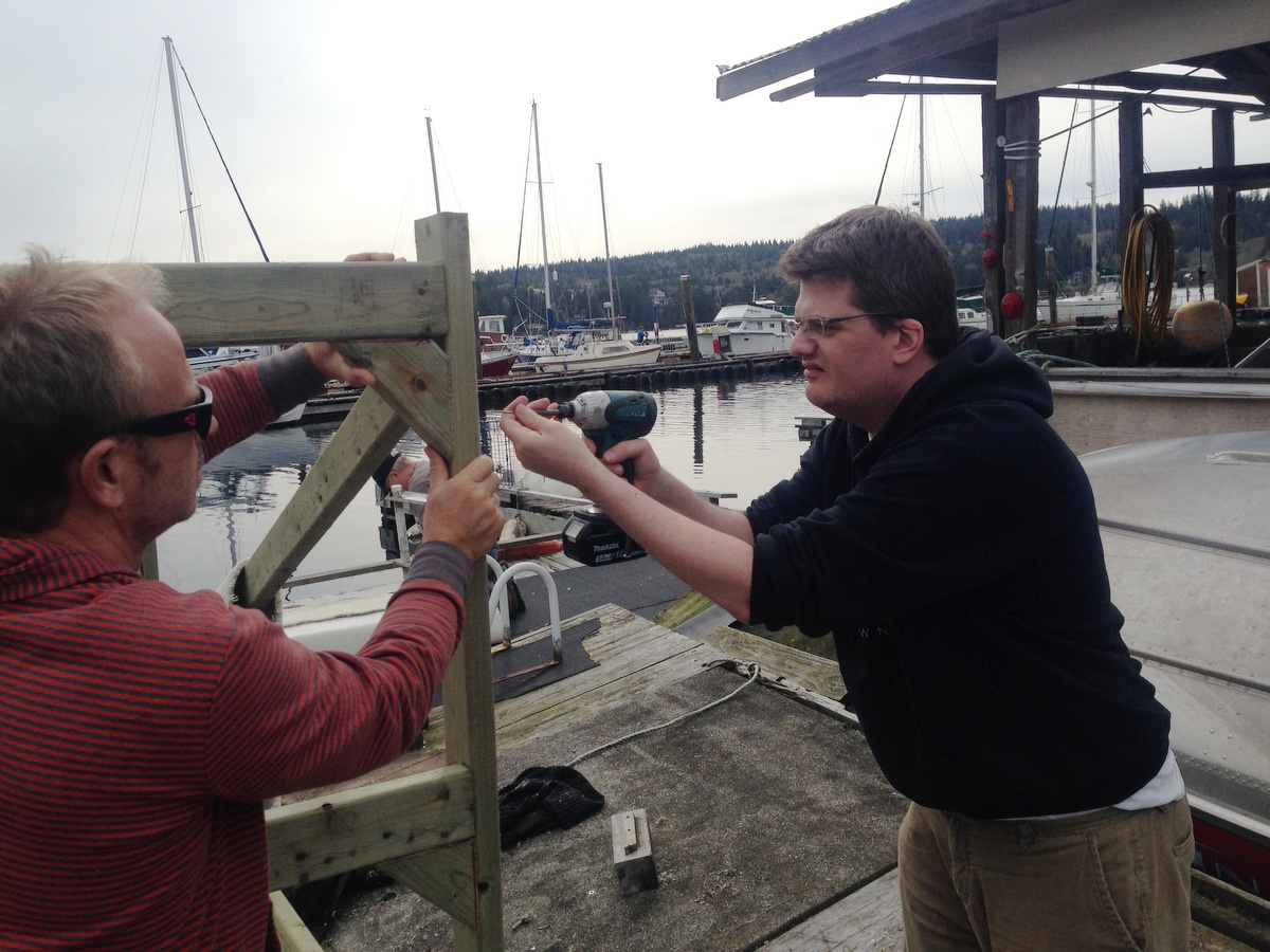 Robert and Gregor screw in a brace on the rack.