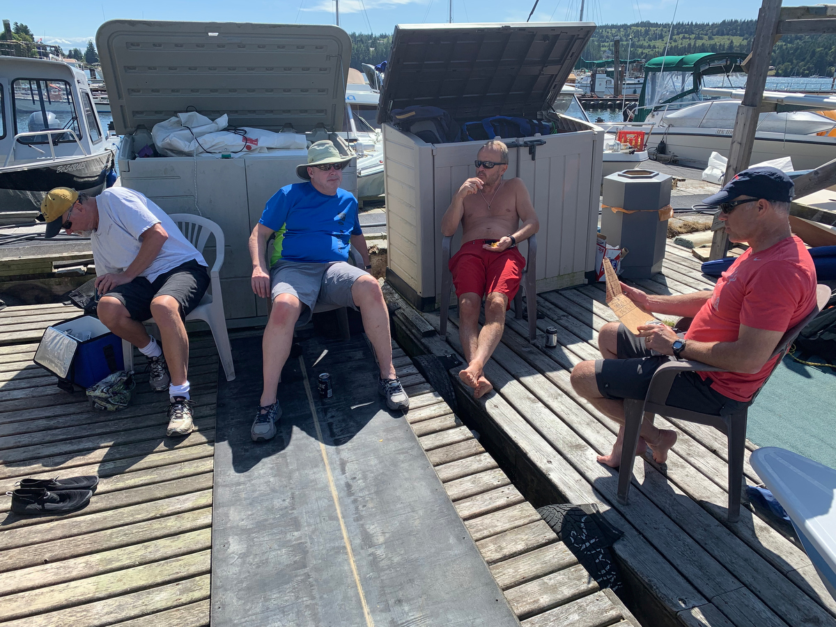 Thomas Andersson, Brian Lyseng and Grzegorz Krolikowski enjoy the shade and some cool drinks as Brian Fournier tabulates the scores from the 2019 Poise Cove Regatta.
