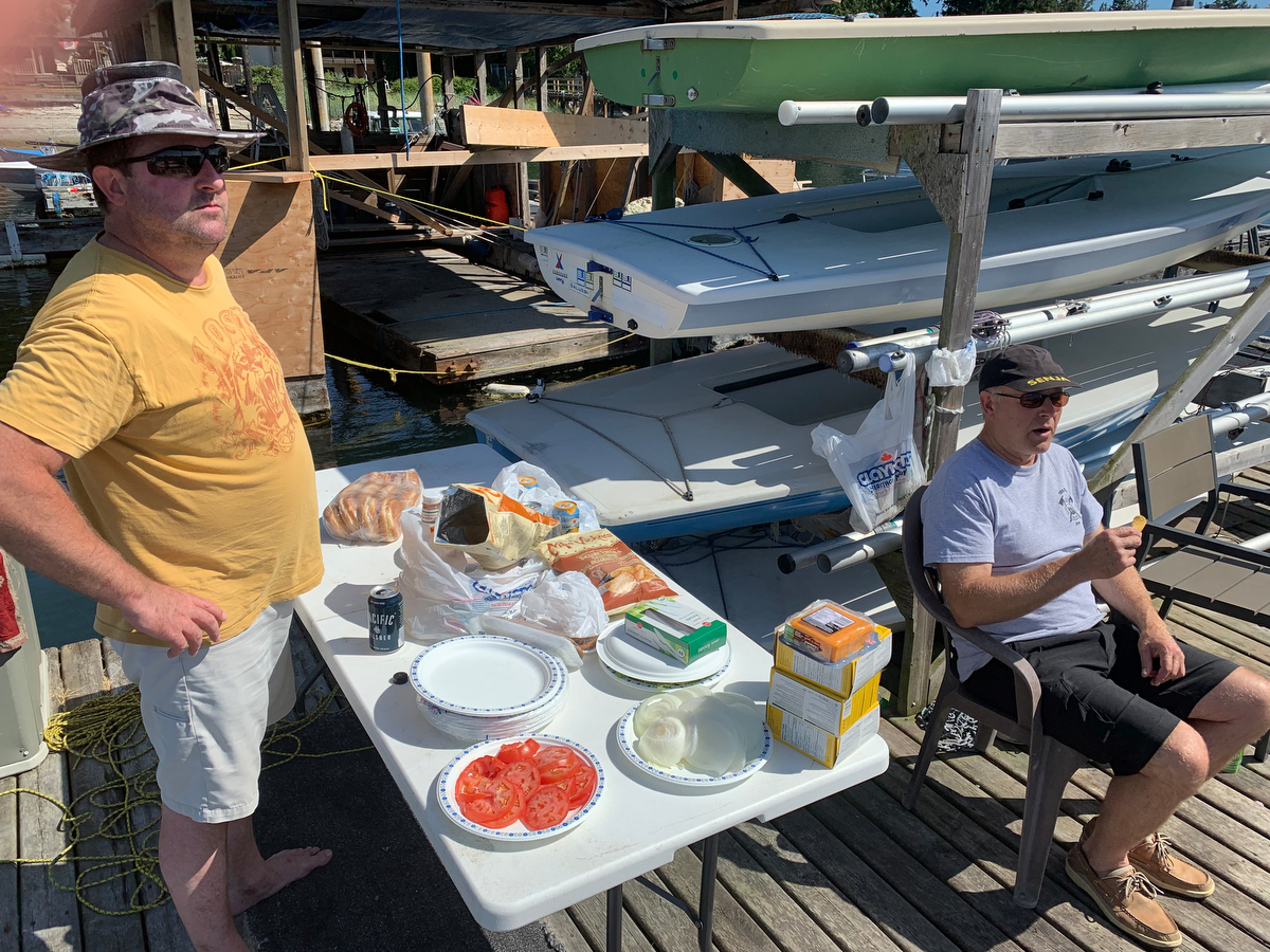 Ken Olson get the fixing ready to go as Dennis Olson speaks about the wind conditions at the 2019 Poise Cove Regatta.