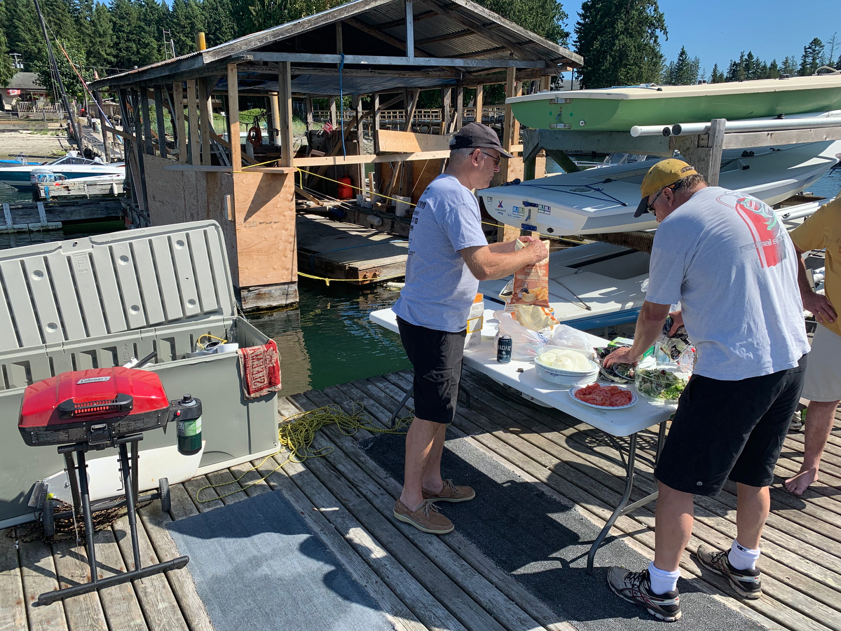 Dennis Olson opening up the chips and Thomas Anderson fixes the salad during the BBQ of the 2019 Poise Cove Regatta